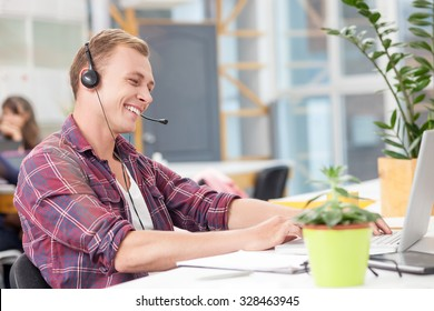 Attractive young operator is typing on laptop in open office. He is sitting at desk and laughing. The man is wearing headphones and talking into microphone