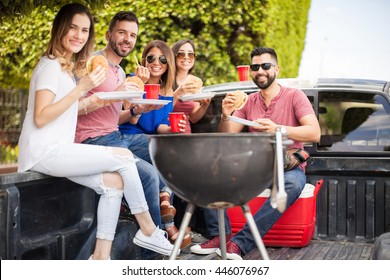 Attractive young people drinking beer and eating burgers next to a grill outdoors and making eye contact