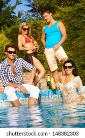Attractive young people enjoying summer holiday by outdoor swimming pool, smiling.