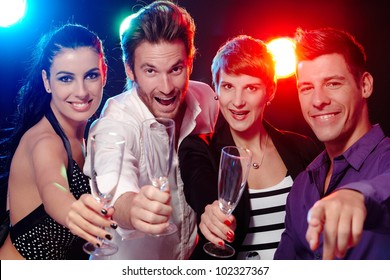 Attractive young people having fun in nightclub, smiling, drinking champagne.