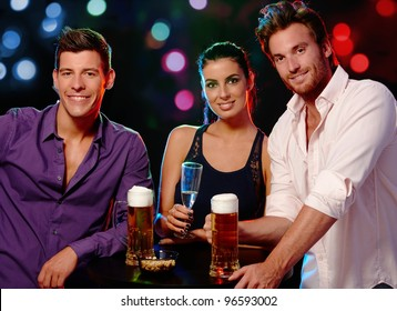 Attractive young people smiling, drinking in nightclub.?