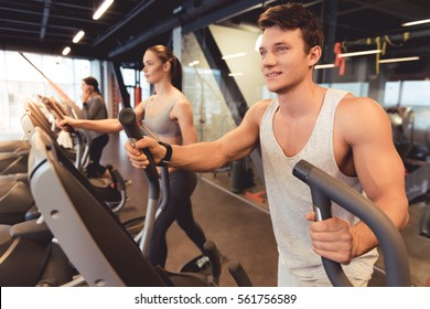 Attractive young people are smiling while working out on an elliptical trainer in gym