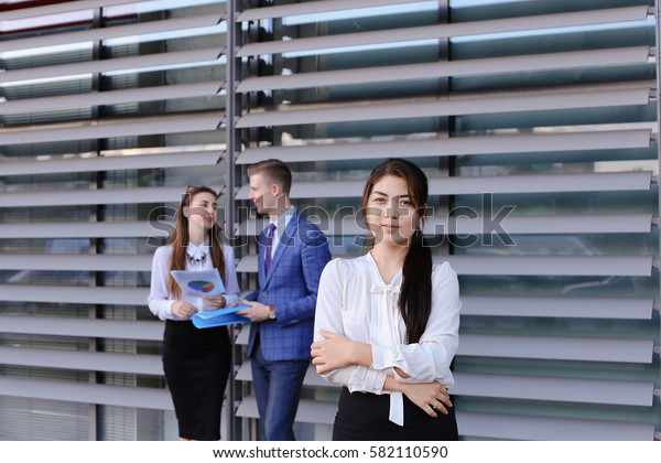 "Attractive young perspective business woman, student rests, took break from work, watching, smiling and posing at camera, enjoys success, shows gesture ""Yes!"" and gesture of thumbs up, holds on head"