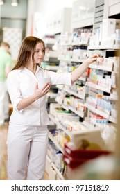 Attractive young pharmacist filling prescription