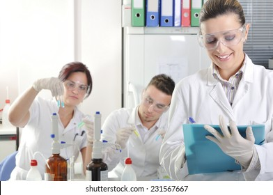 Attractive young PhD student scientist with two colleague out of focus behind her in chemical laboratory