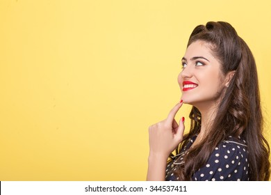 Attractive young pin-up woman is looking forward with interest. She is raising her finger to a chin pensively. The lady is standing and smiling. Isolated and copy space in left side