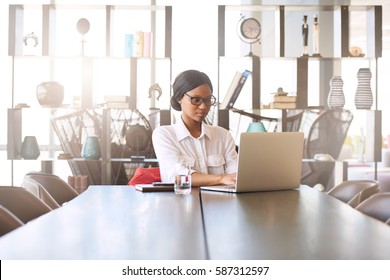 Attractive young professional well educated black woman busy typing on her notebook while seated at her dining room table at home with a large display shelf behind her in the background,.