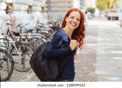 Attractive young redhead woman wearing a backpack leaving a bicycle rank in town turning to give the camera a lovely vivacious smile