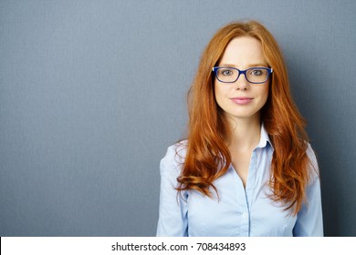 Attractive young redhead woman wearing glasses standing looking at the camera with a quiet smile over a grey studio background with copy space