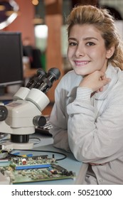 An attractive young researcher sits at a desk with a microscope used to look at electronics. She is smiling towards the camera. Vertical shot.
