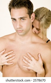 attractive, young, sexy caucasian couple making out against a white background