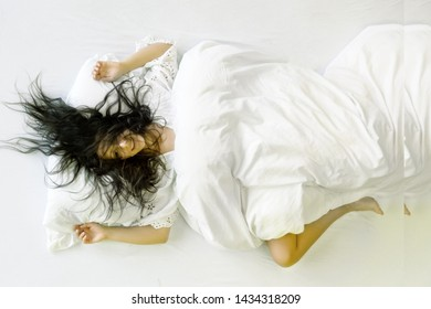 Attractive, young, sexy, dark-haired woman, hair wild on the sheets, mouth open, laughing, lying in fresh soft white sheets in the bedroom with free space for your text, copy space
