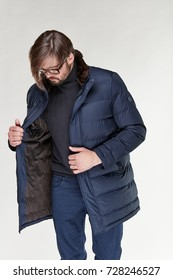 Attractive young sexy man model with beard and glasses posing in dark warm jacket and dark blue pants in light studio