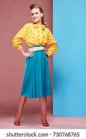 Attractive young sexy smiling woman model wearing yellow blouse with white polka-dot, blue skirt and pink tights in pin-up style, posing in studio with blue and pink background