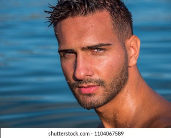 Attractive young shirtless athletic man standing in water in sea or lake, wearing shorts, looking at camera