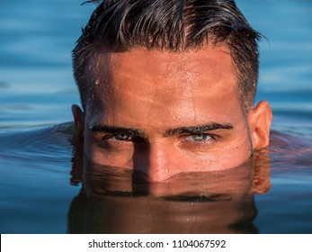 Attractive young shirtless athletic man standing in water in sea or lake, with half face submerged underwater, looking at camera