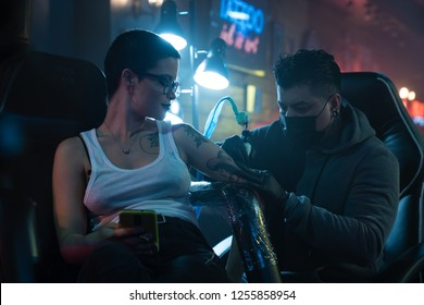 An attractive young and short haired white girl gets a new tattoo done by a proffesional tattoo artist done in her arm during one night at a beaty parlor, tattoo studio or expo.