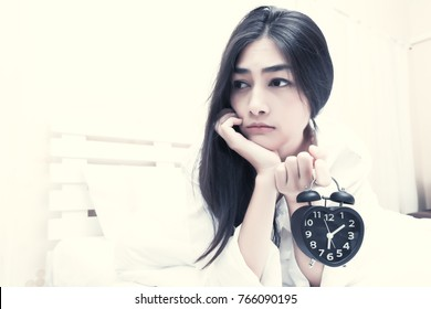Attractive young sleepy asian woman hate to wake up in the morning holding black alarm clock in her finger in bedroom at home. Stress girl having trouble waking up tired from overtime working concept.