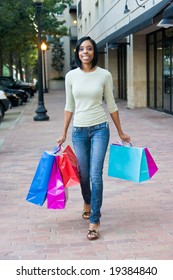 Attractive, young, smiling, African American woman with colorful shopping bags walking in an urban city environment.