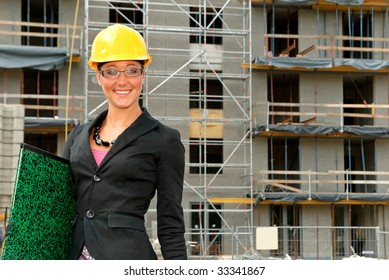 Attractive young smiling female architect, businesswoman in front of construction site.  studio shot.