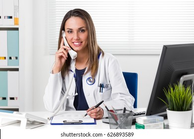 Attractive young smiling female Doctor with stethoscope around neck sat at desk with telephone to ear; Looking at Camera