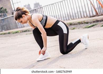 Attractive young sports woman sitting on knee and tying shoe laces on sneakers while having rest during morning jog outdoors. Beautiful fitness girl in stylish sportswear ties shoelace on sports shoes