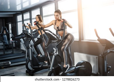 Attractive young sports woman is working out in gym. Doing cardio training on treadmill. Running on treadmill.