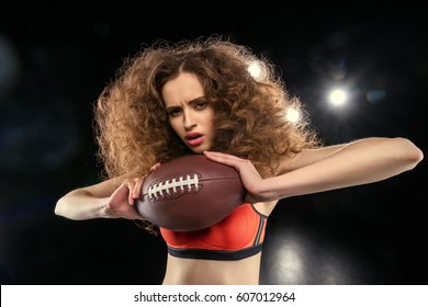 Attractive young sportswoman with culry hair holding rugby ball