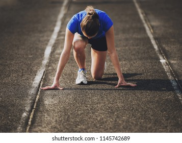 Attractive Young Sporty Girl Ready to Run Sprint. Female Athlete in Powerful Starting Line Pose. Healthy Lifestyle Concept. Training of Athletic Woman. Oudoor Sports. Summer Training. Fitness Girl.