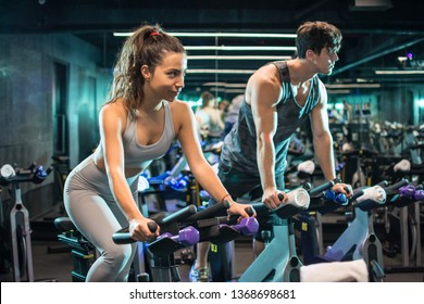 Attractive young sporty woman and handsome muscular man doing spinning on cycling bikes