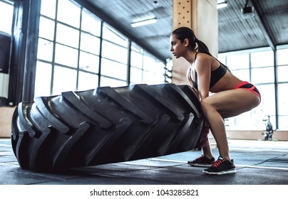 Attractive young sporty woman is working out in gym. Cross fit training. Pushing big tire.