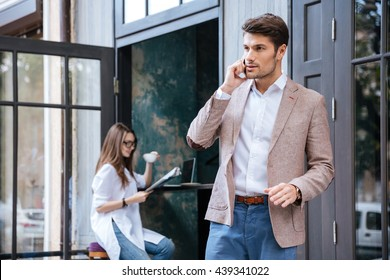 Attractive young stylish businessman talking on the mobile phone outdoors at the cafe
