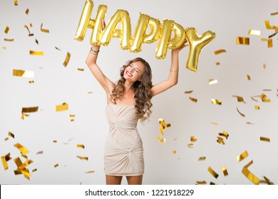 attractive young stylish woman celebrating new year, holding happy air balloons, golden confetti flying, smiling happy, white background, isolated, wearing party dress, makeup and hairstyle