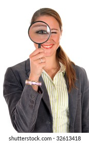 Attractive young successful female businesswoman with magnifying glass.  studio shot.