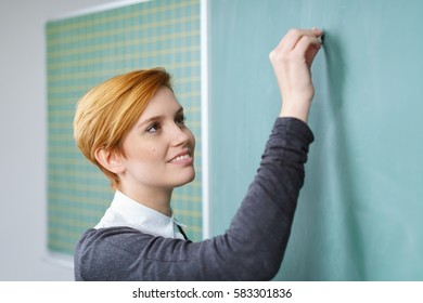 Attractive young teacher or student writing on a blank chalk board in the classroom during a class, close up head and shoulders