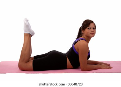Attractive young teen aboriginal ethnicity brunette girl wearing fitness attire laying flat on stomach with legs bent on a pink yoga mat over white