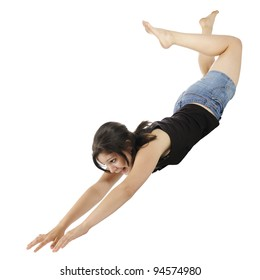 An attractive young teen mid-air, falling (or flying) with hands and head first.  On a white background.