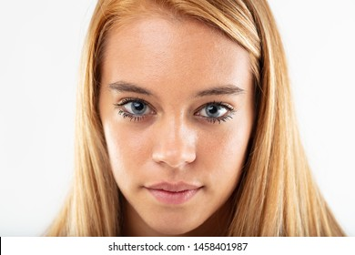 Attractive young teenage girl with long straight blond hair staring intently at the camera in a cropped head shot on white