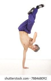 Attractive young topless male dancer sitting on one hand, performing breakdance position , wearing ultraviolet pants, with crossed legs up. Vertical image in studio, on white background