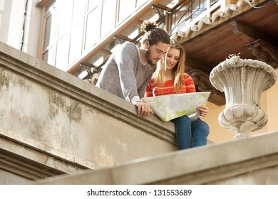Attractive young tourist couple sitting on top of an old city stairs looking at an open street map while on holiday.