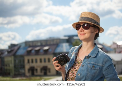 Attractive young tourist girl with camera looking at city's sights