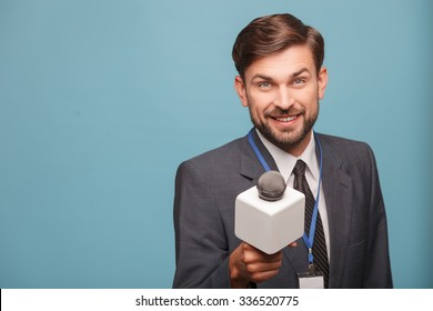 Attractive young tv journalist is interviewing someone with joy. He is standing and stretching a microphone forward. The man is looking at camera and smiling. Isolated and copy space in left side