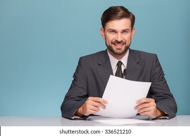 Attractive young tv newscaster is reporting news. He is sitting at the desk in a studio. The man is looking at camera and smiling. Isolated on blue background and copy space in left side