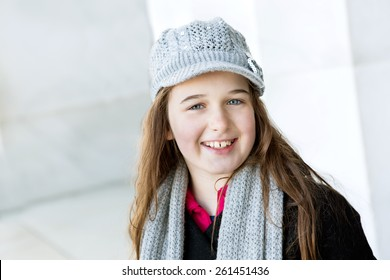 A attractive young tween dressed in winter coat and wool hat smiles at the camera.