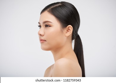 Attractive young Vietnamese woman, isolated on light grey