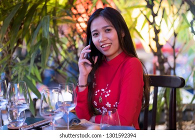 An attractive young Vietnamese woman sitting at a restaurant table outdoors and making a phone call