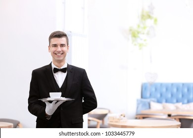 Attractive young waiter holding tray with cup of coffee indoors
