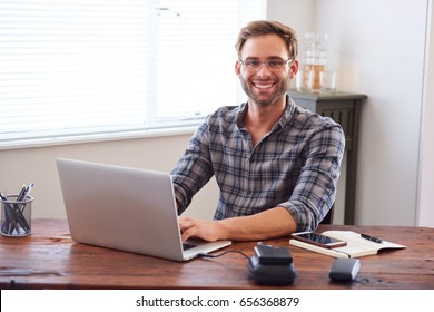 Attractive young, well groomed caucasian male entrepreneur and businessman smiling at the camera with his hands on the keyboard of his laptop computer.