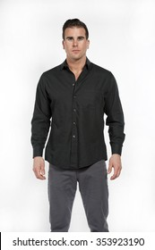 Attractive young white caucasian male model wearing a black formal shirt and gray pants posing in a studio on a white background while looking at the camera.