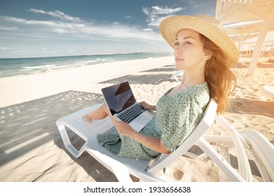 An attractive young white woman in a green dress and hat is resting on a lounger under an umbrella with a laptop in her hands on a sandy sunny beach near the ocean. Freelance and remote work